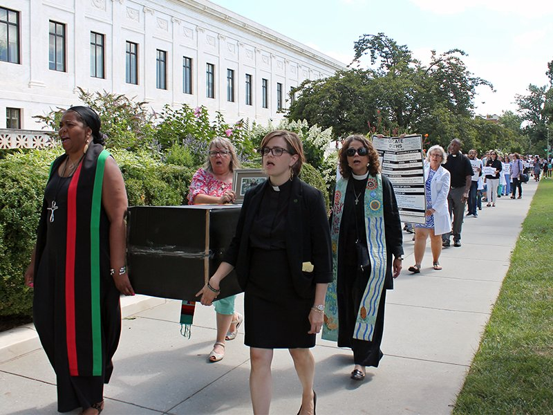 Interfaith clergy carry a cardboard coffinwhile leading a procession to protest attempts to repeal the Affordable Care Act during a rally on Capitol Hill in Washington, D.C., on July 25, 2017. RNS photo by Madeleine Buckley