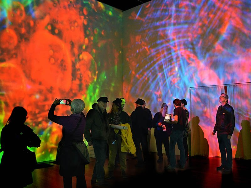 """Guests view the Bill Ham Light Painting Room/Light Show during the opening night of """"TheSummer of Love Experience: Art, Fashion, and Rock & Roll"""" exhibit at the de Young Museum in San Francisco on April 8, 2017.  Photo courtesy of BillHamLights.com"""
