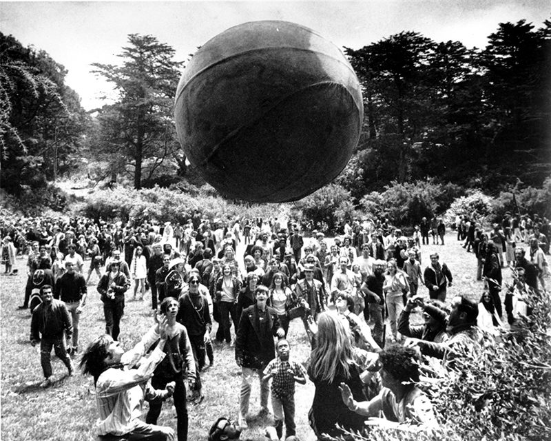A crowd keeps a large ball, painted to represent a world globe, in the air during a gathering at Golden Gate Park in San Francisco, to celebrate the summer solstice on June 21, 1967, day one of