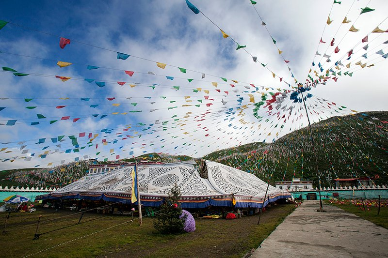 The Pure Land prayer festival takes place in and around a huge Tibetan nomad tent decorated with traditional patterns. RNS photo by Alexandra Radu & A Buddhist prayer festival fills a remote Tibetan village with ...