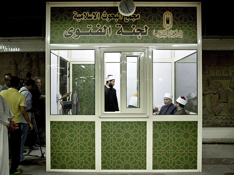 Al-Azhar clerics wait to answer commuters' questions inside a Fatwa Kiosk at the al-Shohada metro station on July 25, 2017, in Cairo. Egypt's Al-Azhar institute, the Sunni Muslim world's foremost religious institution, set up the booth with clerics offering fatwas, or religious advice, to commuters. (AP Photo/Nariman El-Mofty, File)
