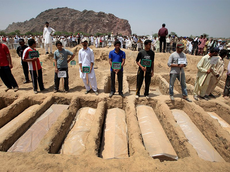Members of the Ahmadi Muslim community hold the names of victims as they stand over their graves in Chenab Nagar, located in Punjab's Chiniot District, about 125 miles northwest of Lahore, Pakistan, on May 29, 2010.  Chenab Nagar, also known as Rabwah, is the headquarters for the Ahmadiyya community in Pakistan. Photo via Reuters