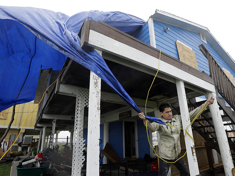 Shawn Hagdorn helps to cover the roof of his father's home that was damaged in the wake of Hurricane Harvey, on Aug. 28, 2017, in Rockport, Texas. (AP Photo/Eric Gay)