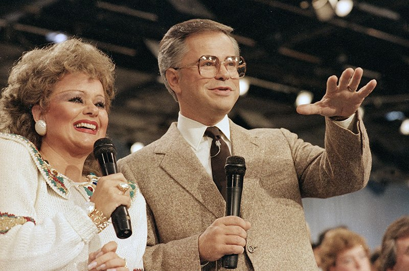 Tammy Faye Bakker and her then-husband, television evangelist Jim Bakker, talk to their TV audience at their PTL ministry near Fort Mill, S.C., in this Aug. 20, 1986 file photo. (AP Photo/Lou Krasky, file)