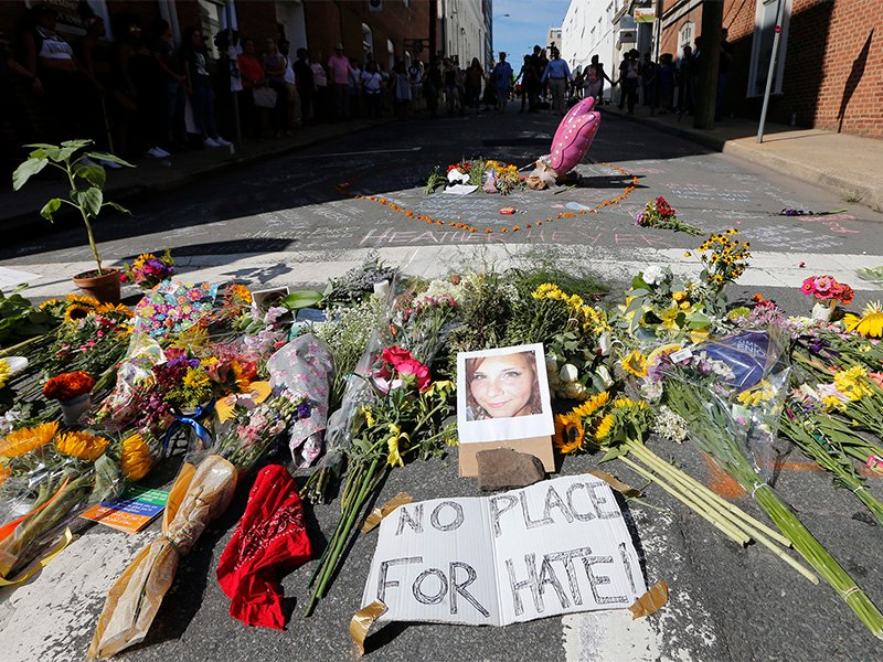 A makeshift memorial of flowers and a photo of victim Heather Heyer sits in Charlottesville, Virginia, on Aug. 13, 2017. Heyer died when a car rammed into a group of people who were protesting the presence of white supremacists who had gathered in the city for a rally. AP Photo/Steve Helber