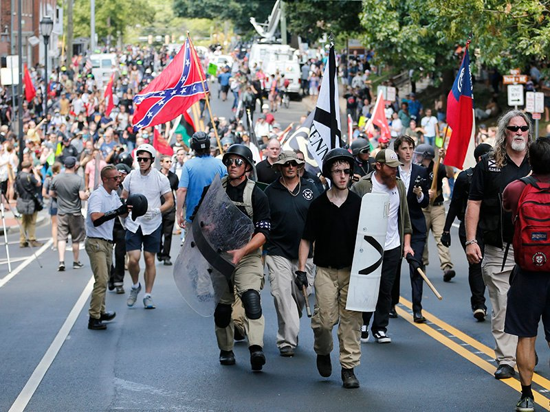 White nationalist demonstrators walk through town after their rally was closed down near Lee Park in Charlottesville, Va., on Aug. 12, 2017. (AP Photo/Steve Helber)