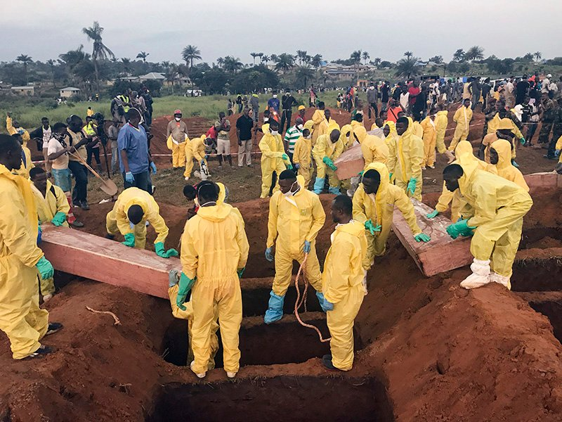 Volunteers inter coffins during a mass funeral for victims of heavy flooding and mudslides in Regent at a cemetery in Freetown, Sierra Leone, on Aug. 17, 2017. (AP Photo/ Manika Kamara)