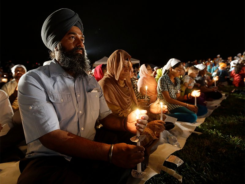 Raghu Vinder listens to speakers during a candlelight vigil in the parking lot of the Sikh Temple of Wisconsin on Aug. 5, 2013, in Oak Creek, Wis., marking the one-year anniversary of the shooting rampage in which a white supremacist killed six people. (AP Photo/Morry Gash)