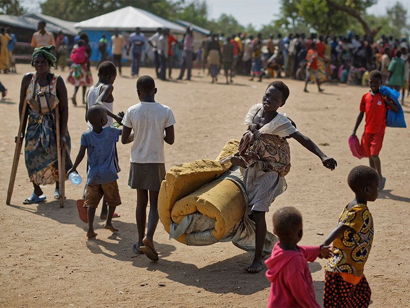 A South Sudanese refugee female with a baby on her back carries a foam mattress to the communal tent where they will sleep, at the Imvepi reception center, where newly arrived refugees are processed before being allocated plots of land in nearby Bidi Bidi refugee settlement, in northern Uganda, on June 9, 2017. The number of South Sudanese refugees sheltering in Uganda has reached 1 million, the United Nations said on Aug. 17, 2017, a grim milestone in what has become the world's fastest-growing refugee crisis. (AP Photo/Ben Curtis)