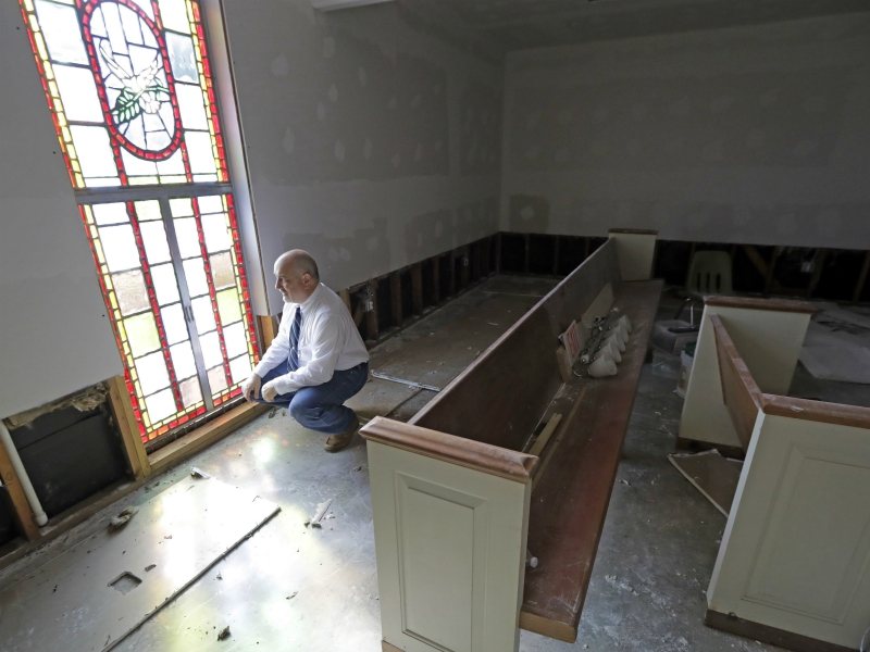 Pastor Jeffrey Willey kneels inside the Christ United Church, which was flooded in the aftermath of Hurricane Harvey, on Sept. 3, 2017, in Cypress, Texas. The church, which also flooded last year, had just recovered before Harvey caused more damage. (AP Photo/David J. Phillip)
