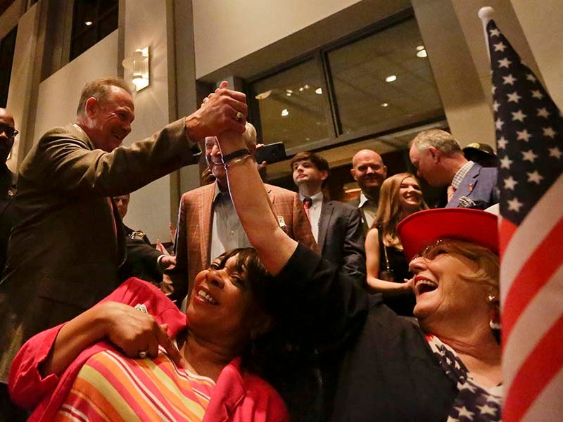 Former Alabama Chief Justice and U.S. Senate candidate Roy Moore greets supporter Patricia Jones, right, before his election party Sept. 26, 2017, in Montgomery, Ala. AP Photo/Brynn Anderson