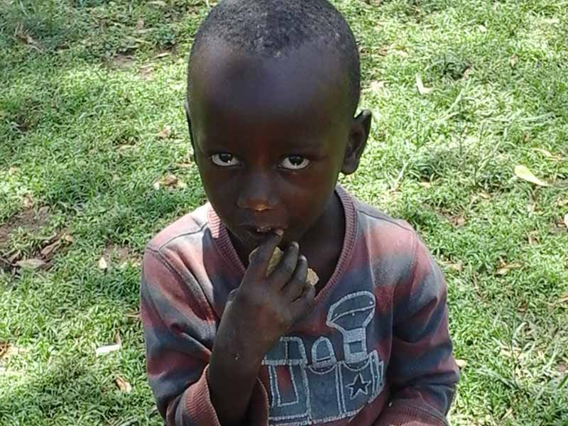 A child eats biscuit in the town of Kataba near Kampala, Uganda on August 22, 2017. Children here continue to live in constant fear of being kidnapped and sacrificed. Kidnappers or witchdoctors have been accused of using biscuits and soda to seduce children. Photo by Doreen Ajiambo