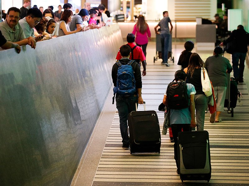 Travelers make their way up the arrival ramp at the Tom Bradley International Terminal at the Los Angeles International Airport on June 29, 2017. After months of wrangling, tighter restrictions on travel to the U.S. from six mostly Muslim nations took effect in June after the Supreme Court gave its go-ahead for a limited version of President Trump's plans for a ban. AP Photo/Jae C. Hong