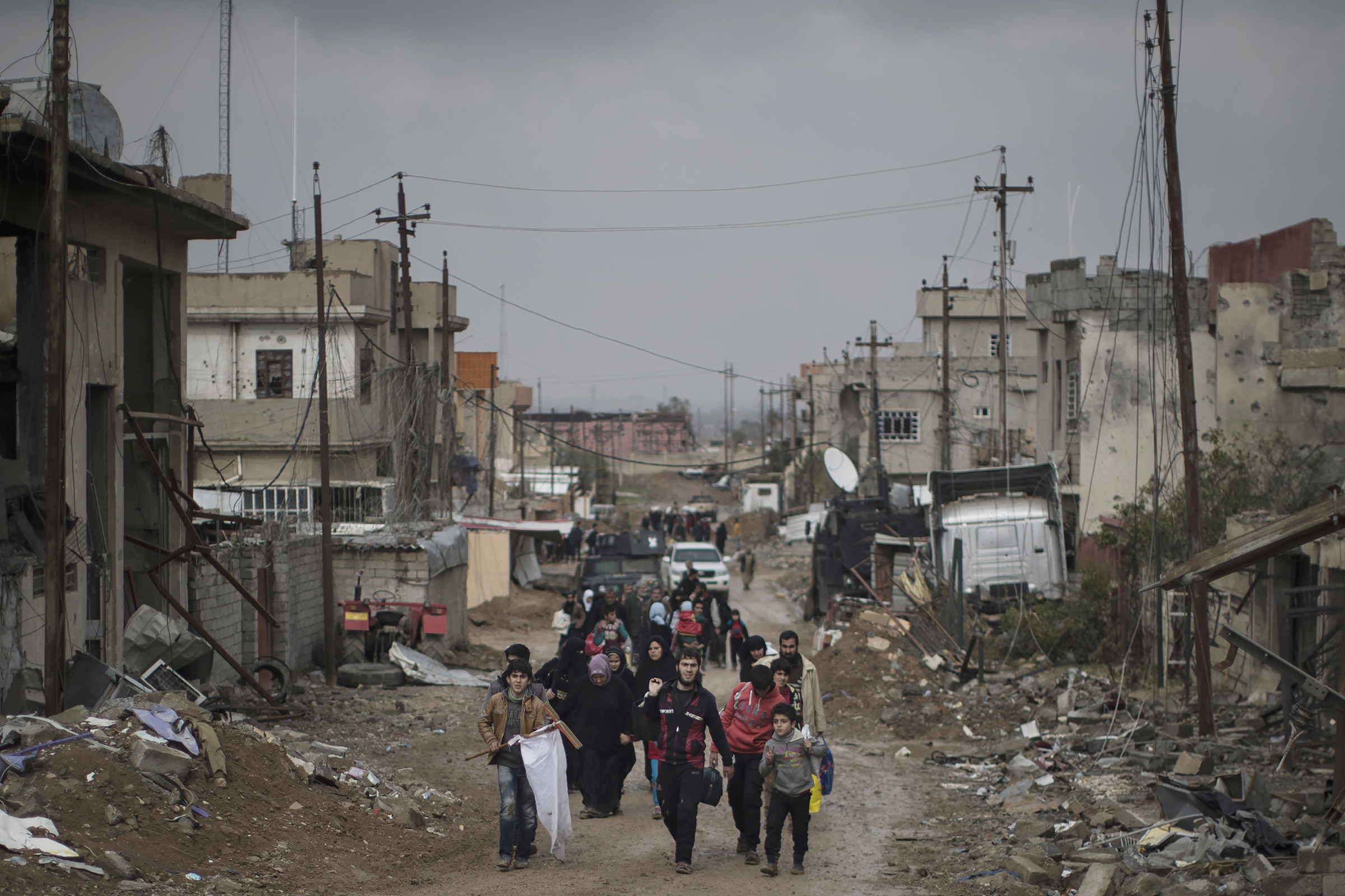 In this March 13, 2017 file photo, Iraqi civilians flee their homes during fighting between Iraqi security forces and Islamic State militants, on the western side of Mosul, Iraq. 3,351,132 _ The number of Iraqis across the country who remained displaced by violence in the fight against IS as of June 30, according to the U.N. migration agency. As Iraqi forces have retaken territory from the militants, more than 1,952,868 people have been able to return home. Of those still displaced, the vast majority are from Nineveh province, where Mosul is located. Some 700,000 are sheltering in camps, while the rest are living with extended family or in rented housing. AP Photo/Felipe Dana, File