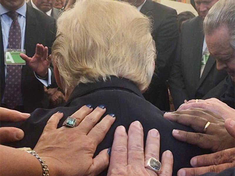 Evangelical supporters place hands on and pray with President Trump in the Oval Office of the White House. Photo courtesy of Johnnie Moore