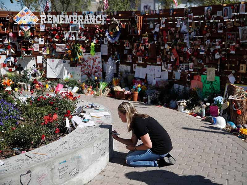 Jenni Tillett writes a message at the Las Vegas Community Healing Garden, Monday, Oct. 16, 2017, in Las Vegas. The garden was built as a memorial for the victims of the recent mass shooting in Las Vegas. AP Photo/John Locher