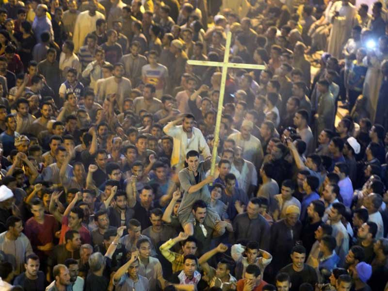 In this May 26, 2017 file photo, Coptic Christians shout slogans after the funeral service of some of the victims of a bus attack, at Abu Garnous Cathedral in Minya, Egypt. Amr Nabil/AP