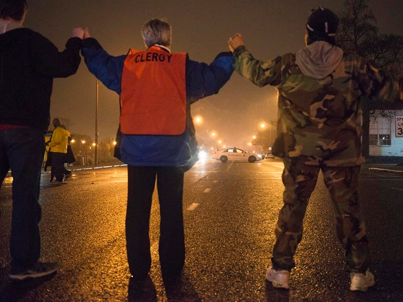 A clergy member holds hands with protesters as they shut down a street in St. Louis on Nov. 23, 2014. Photo by Justin L. Stewart