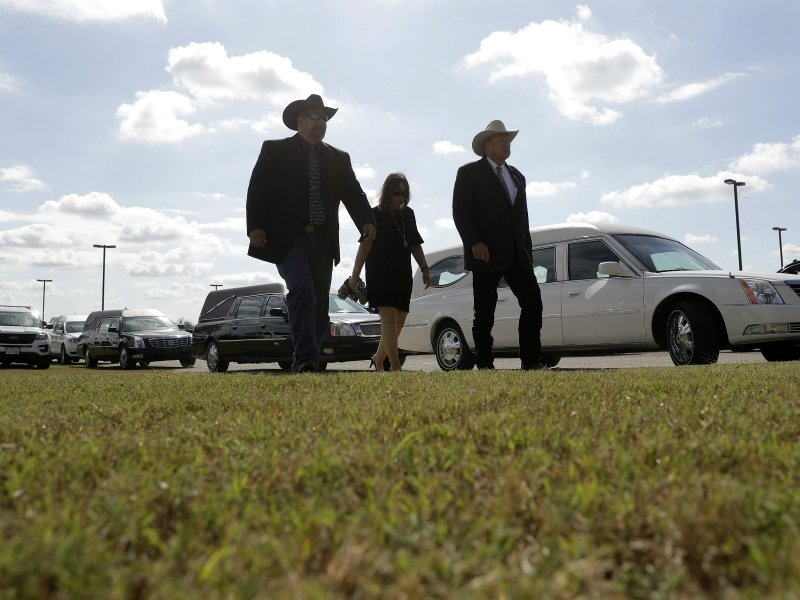 Mourners walk past a line of hearses as they arrive Nov. 15, 2017, for a funeral for members of the Holcombe family who were killed in the Sutherland Springs Baptist Church shooting in Floresville, Texas. A man opened fire inside the church in the small South Texas community last week, killing more than two dozen. (AP Photo/Eric Gay)