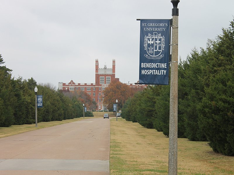 A banner touting Benedictine hospitality greets visitors to St. Gregory's University, a Catholic liberal arts university near Shawnee, Okla. The century-old Benedictine Hall, seen in the background, is a landmark at St. Gregory's, which will close in December. RNS photo by Bobby Ross Jr.