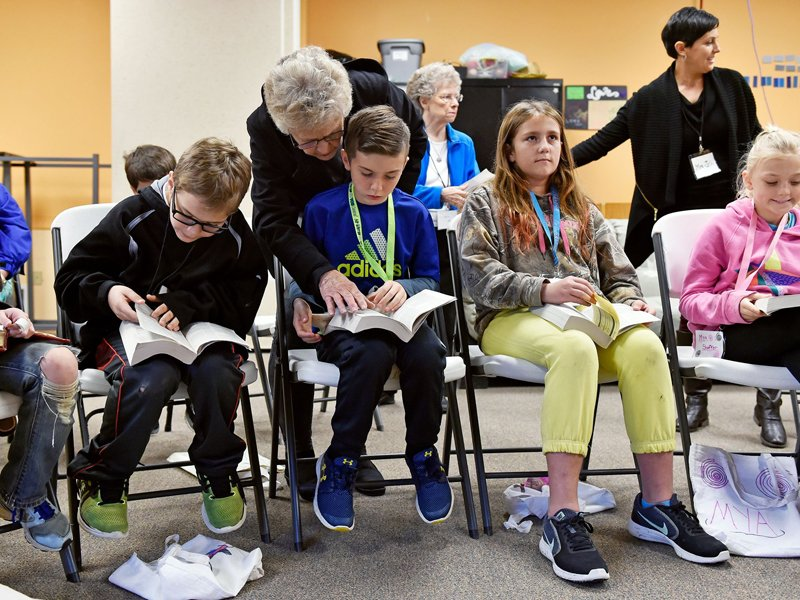 Volunteer Carol Corwell, back, helps Hunter Naugle, 10, find a verse in his Bible during released time Nov. 9, at Valley View Alliance Church in Hellam, Pa. Photo: Chris Dunn, York (Pa.) Daily Record)