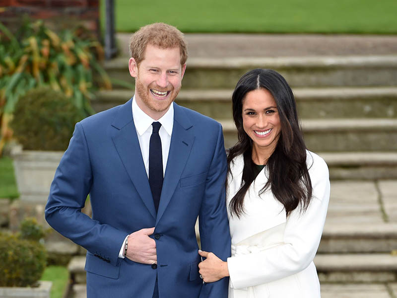 Britain's Prince Harry and Meghan Markle pose for the media in the grounds of Kensington Palace in London, Monday Nov. 27, 2017. It was announced Monday that Prince Harry, fifth in line for the British throne, will marry American actress Meghan Markle in the spring, confirming months of rumors. (Eddie Mulholland/Pool via AP)