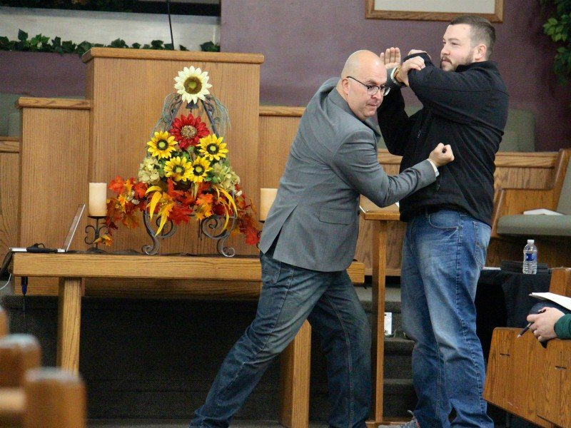 Barry Young, vice president of Church Security Ministries at Strategos, demonstrates using a tactical pen for self-defense on Marc Anderson of Kalamazoo, Mich., at an intruder awareness and response training Nov. 11, 2017, at Prairie Baptist Church in Scotts, Mich. RNS photo by Emily McFarlan Miller