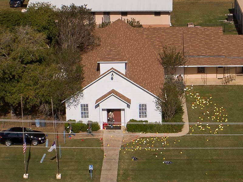 Flags mark evidence on the lawn of the First Baptist Church in Sutherland Springs, Texas, on Nov. 6, 2017, a day after over 20 people died in a mass shooting. (Jay Janner/Austin American-Statesman via AP)