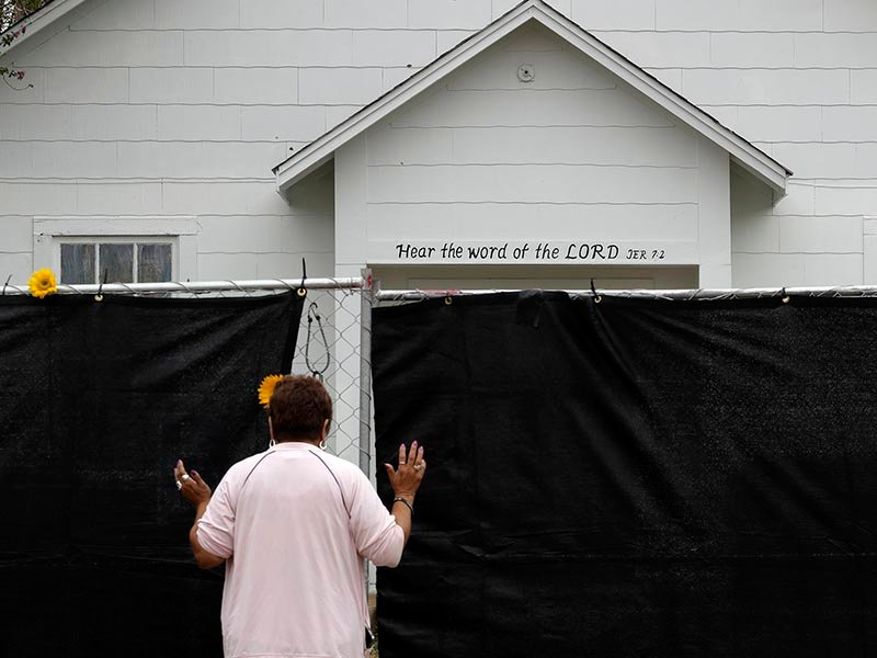 A woman prays outside of the Sutherland Springs First Baptist Church in Sutherland Springs, Texas, on Nov. 12, 2017, a week after a man opened fire inside the church. Hundreds of people gathered in the tiny town for a Sunday service at a tent erected in a baseball field. (AP Photo/Eric Gay; caption amended by RNS)