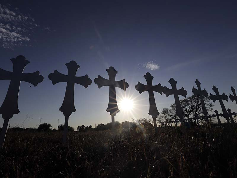 The sun sets behind 26 crosses placed in a field before a vigil Nov. 6, 2017, for the victims of the First Baptist Church shooting in Sutherland Springs, Texas. Texas officials confirmed Devin Patrick Kelley as the shooter who killed 26 people and wounded about 20 others at the church. (AP Photo/David J. Phillip)