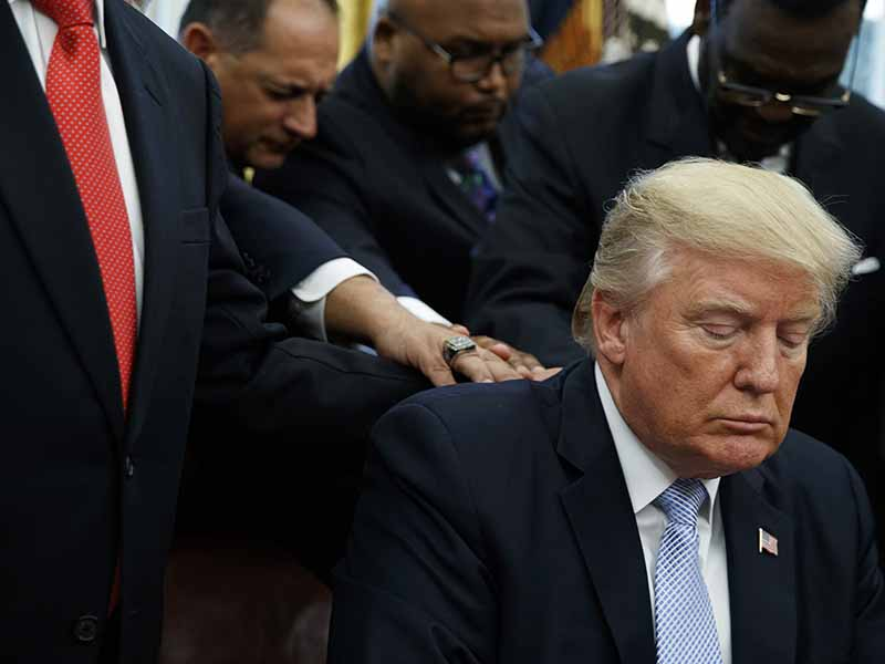 Faith leaders pray with President Trump after he signed a proclamation for a national day of prayer to occur on Sept. 3, 2017, in the Oval Office of the White House on Sept. 1, 2017, in Washington. (AP Photo/Evan Vucci)