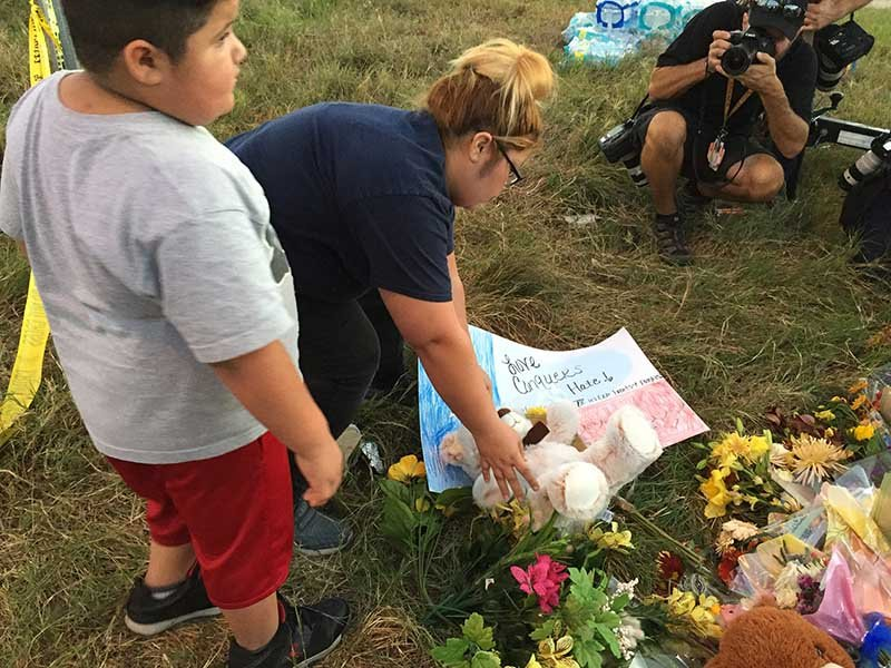Jennifer Garcia and son Jayden, 6, lay a poster with the words