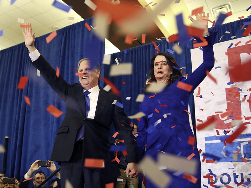 Democratic candidate for U.S. Senate Doug Jones and his wife, Louise, wave to supporters before speaking during an election-night watch party Tuesday, Dec. 12, 2017, in Birmingham, Ala. In a stunning victory aided by scandal, Jones won Alabama's special Senate election on Tuesday, beating back history, an embattled Republican opponent and President Trump, who urgently endorsed GOP rebel Roy Moore despite a litany of sexual misconduct allegations. (AP Photo/John Bazemore)