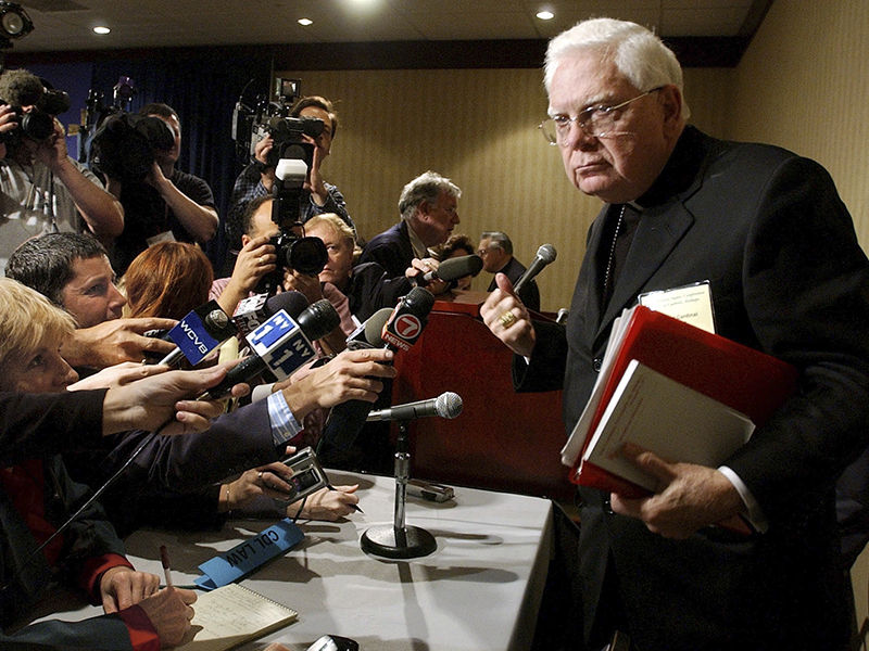 In this Tuesday, Nov. 12, 2002, file photo, Cardinal Bernard Law, right, departs a news conference during the second day of the U.S. Conference of Catholic Bishops' annual meeting in Washington. Law, who recently had been hospitalized in Rome, died early Wednesday.Law stepped down under pressure in 2002 over his handling of clergy sex abuse cases. (AP Photo/Ken Lambert, File) (Caption amended by RNS)