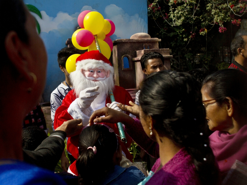 a man dressed as santa claus distributes sweets to the devotees after the christmas prayers at a church in gauhati india monday dec 25 2017