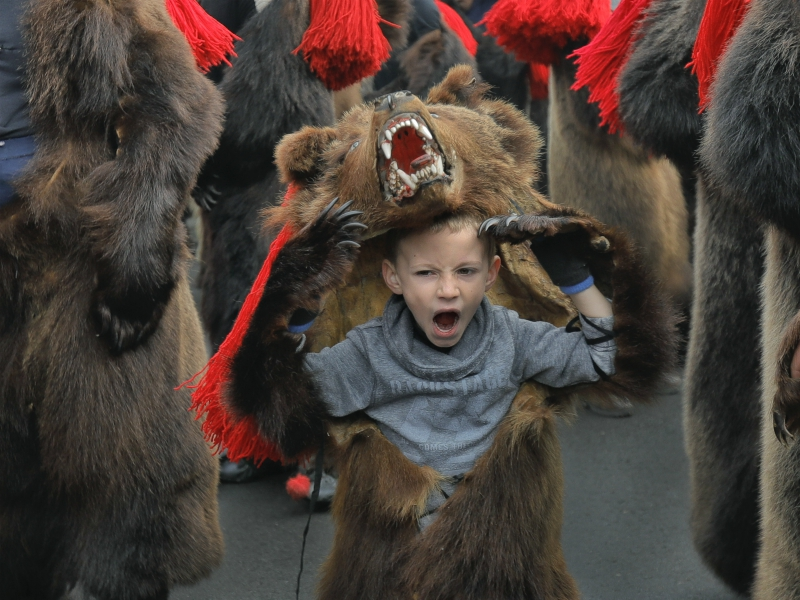 A child wearing a bear fur costume yawns during a parade of New Year's rituals in Comanesti, northern Romania, Saturday, Dec. 30, 2017. The tradition originated in pre-Christian times, when dancers in costumes or animal furs went from house to house in villages singing and dancing to ward off evil.(AP Photo/Vadim Ghirda) (Caption amended by RNS)