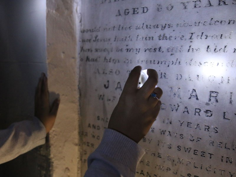 Tourists slowly file into the dim space, some holding up their electric tea lights to read the inscriptions on the vaults. RNS photo by Samantha Maldonado