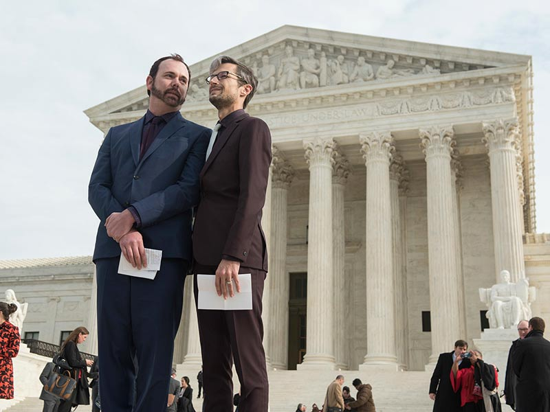 The original plaintiffs in the Masterpiece Cakeshop case — Charlie Craig, left, and David Mullins — wait to address supporters after oral arguments at the Supreme Court on Dec. 5, 2017, in Washington. The Human Rights Campaign and coalition supporters rallied against what they called a license to discriminate at the court. (Kevin Wolf/AP Images for Human Rights Campaign)