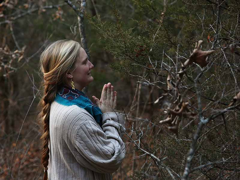 In preparation for the Yule celebration, Darcy Higgins asks a tree for permission to cut it down so it may serve as the Yule tree at Oak Spirit Sanctuary in Boonville, Mo., on Dec. 16, 2017. Higgins said that she always asks permission before harvesting plants or trees and that her own feelings let her understand the plant's response, as do ecological indicators — such as how well the plant is thriving in its current environment and how well the environment would do without the plant. RNS photo by Mikala Compton