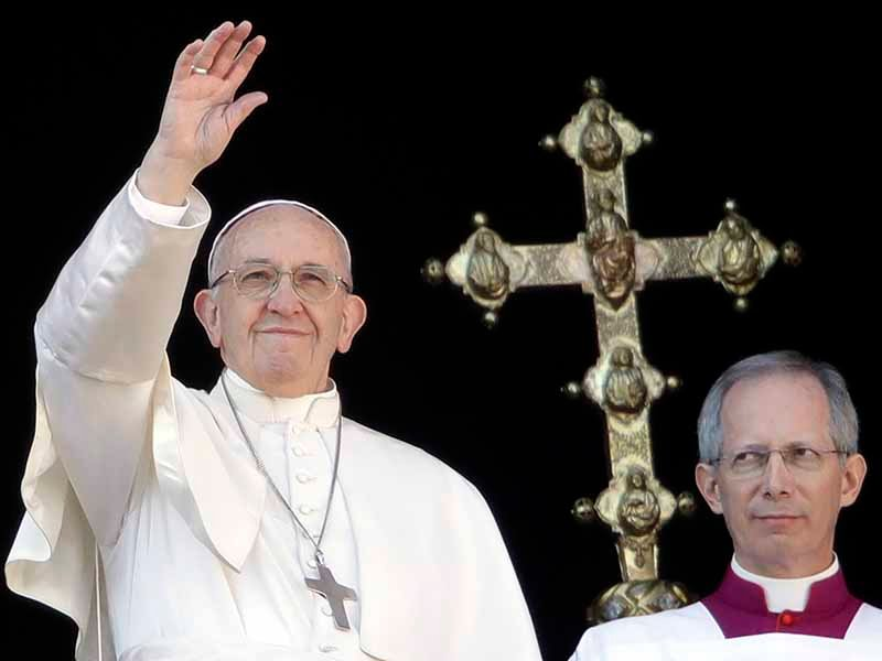 Pope Francis, flanked by Master of Ceremonies Bishop Guido Marini, waves to the faithful during the Urbi et Orbi (Latin for