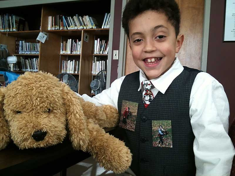 Tain Gregory, age 8 in this photo, wears pictures on his vest of his godbrother, Ben, who was killed at Sandy Hook Elementary when a gunman blasted his way into the building. Tain's mother, Sophfronia Scott, printed two photos of Tain and Ben playing in a pile of leaves in her yard after Tain requested to wear them to Ben's funeral. She fastened them with paper clips to Tain's vest. Photo courtesy of Sophfronia Scott