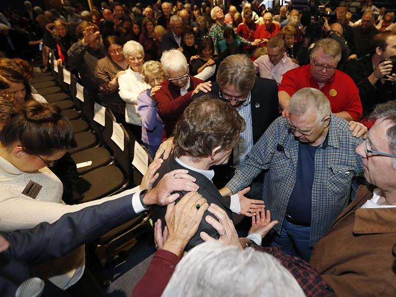 Jack Phillips, lower center, is surrounded by supporters as they offer a prayer for the owner of Masterpiece Cake after a rally on the campus of a Christian college Nov. 8, 2017, in Lakewood, Colo. The small rally was held to build support for Phillips, who is at the center of a case that will be considered by the U.S. Supreme Court in December. The case may determine if business owners like Phillips are having their right of religious liberty and free expression violated by having to offer their wedding services to same-sex couples. (AP Photo/David Zalubowski)