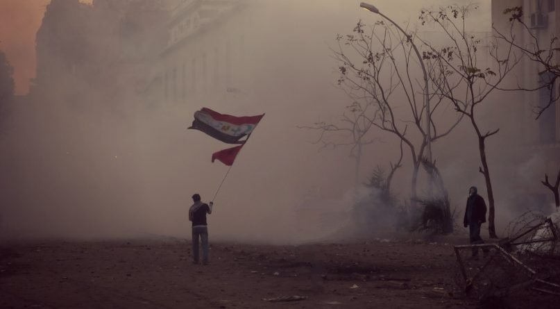 A protester defiantly waves an Egyptian flag with the emblems of Christianity and Islam ( the cross and the crescent ) added - a message of religious unity. Clouds of tear gas are lit up with an eerie glow by the sinking sun. - Courtesy of Alisdare Hickson via Flickr Creative Commons (http://bit.ly/2mhL29P) - Egypt ranks #17 on Open Doors World Watch List
