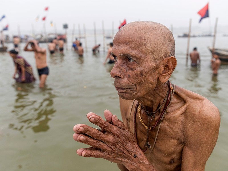 A Hindu devotee offer prayers to the Sun God after taking a ritualistic bath at the Triveni Sangam, the meeting point of the Indian holy rivers the Ganges and the Yamuna, on the auspicious day of