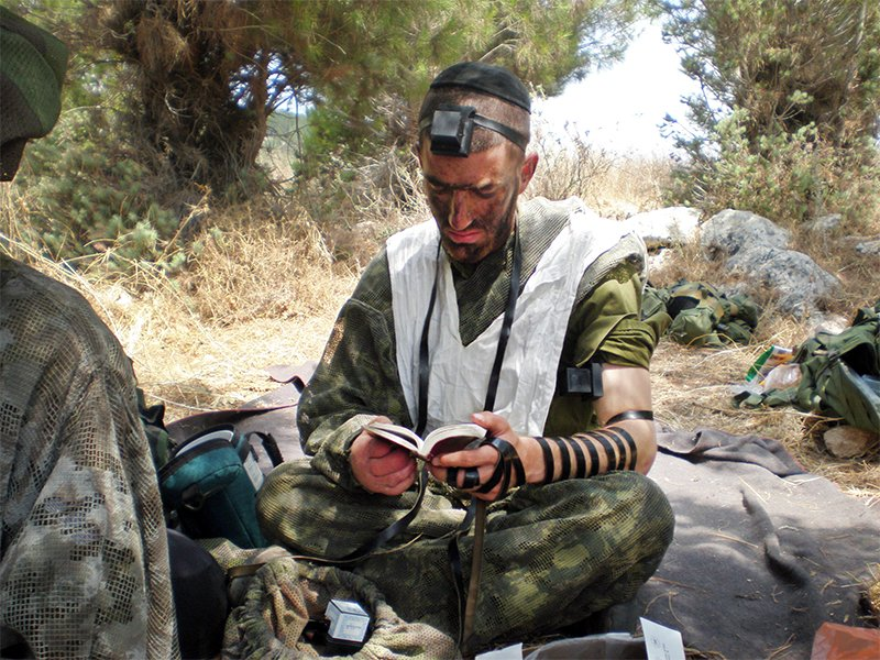 Moshe Lifshitz, a haredi (ultra-Orthodox) Israeli, wears tefillin while praying in the Israeli army. Lifshitz broke with his community's tradition when he chose to enlist in the Israeli army rather than apply for an exemption to study Torah full time. Photo courtesy of Moshe Lifshitz