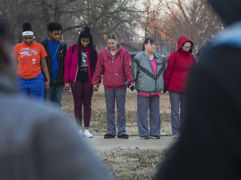 Students and community members hold hands in prayer before classes at Paducah Tilghman High School in Paducah, Ky., Wednesday, Jan. 24, 2018. The gathering was held for the victims of the Marshall County High School shooting on Tuesday. (Ryan Hermens/The Paducah Sun via AP)
