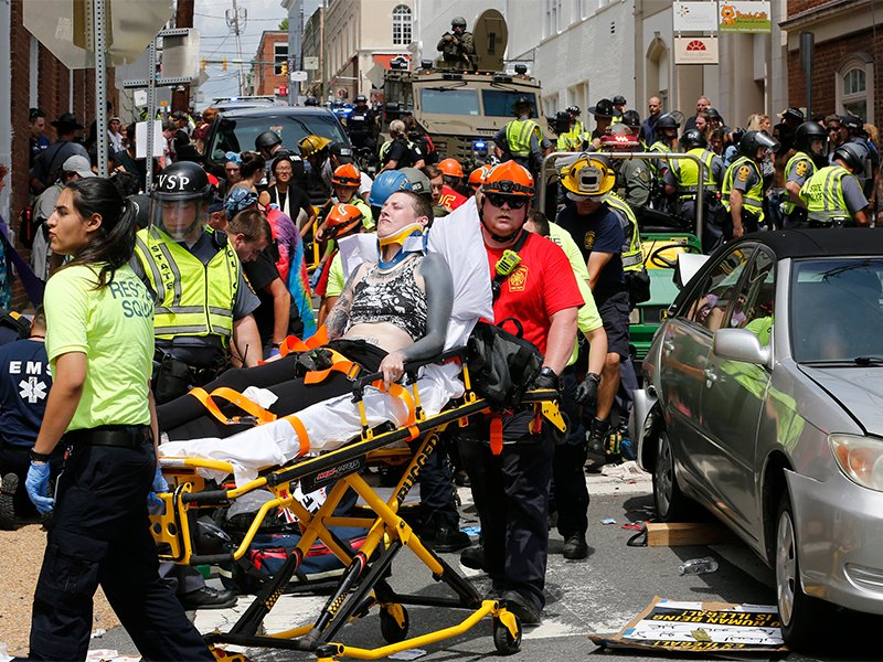Rescue personnel help injured people after a car ran into a large group of protesters after a white nationalist rally in Charlottesville, Va., on Aug. 12, 2017. One person was killed and 19 were injured in the incident. (AP Photo/Steve Helber; caption amended by RNS)