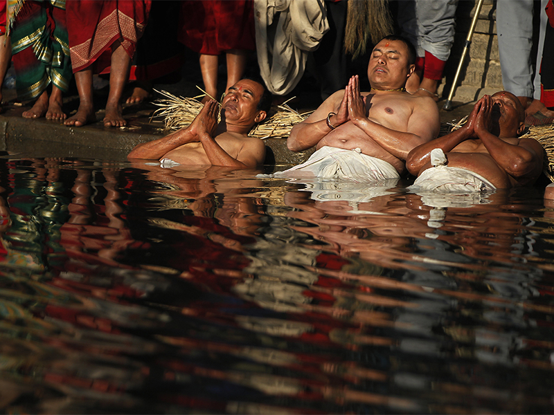 Nepalese Hindu devotees offer prayers while dipping half of their bodies into the Hanumante River during the Madhav Narayan Festival in Bhaktapur, Nepal, on Jan. 2, 2018. During the festival, devotees recite scriptures dedicated to the Hindu goddess Swasthani and Lord Shiva. (AP Photo/Niranjan Shrestha)