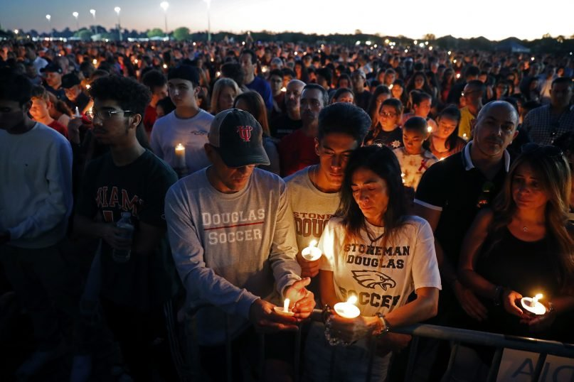 Jorge Zapata, Jr., center, a student at Marjory Stoneman Douglas High School, holds candles with his mother Lavinia Zapata, and father Jorge Zapata, Sr., during a candlelight vigil for the victims of the Wednesday shooting at the school, in Parkland, Fla., Thursday, Feb. 15, 2018. (AP Photo/Gerald Herbert)