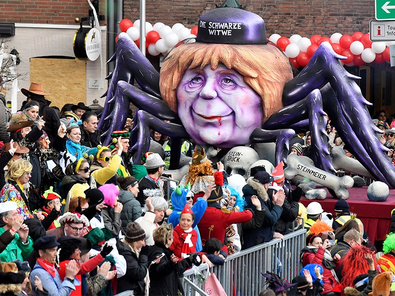 A float depicts German Chancellor Angela Merkel as black widow with the skulls of former political opponents in front and the writing